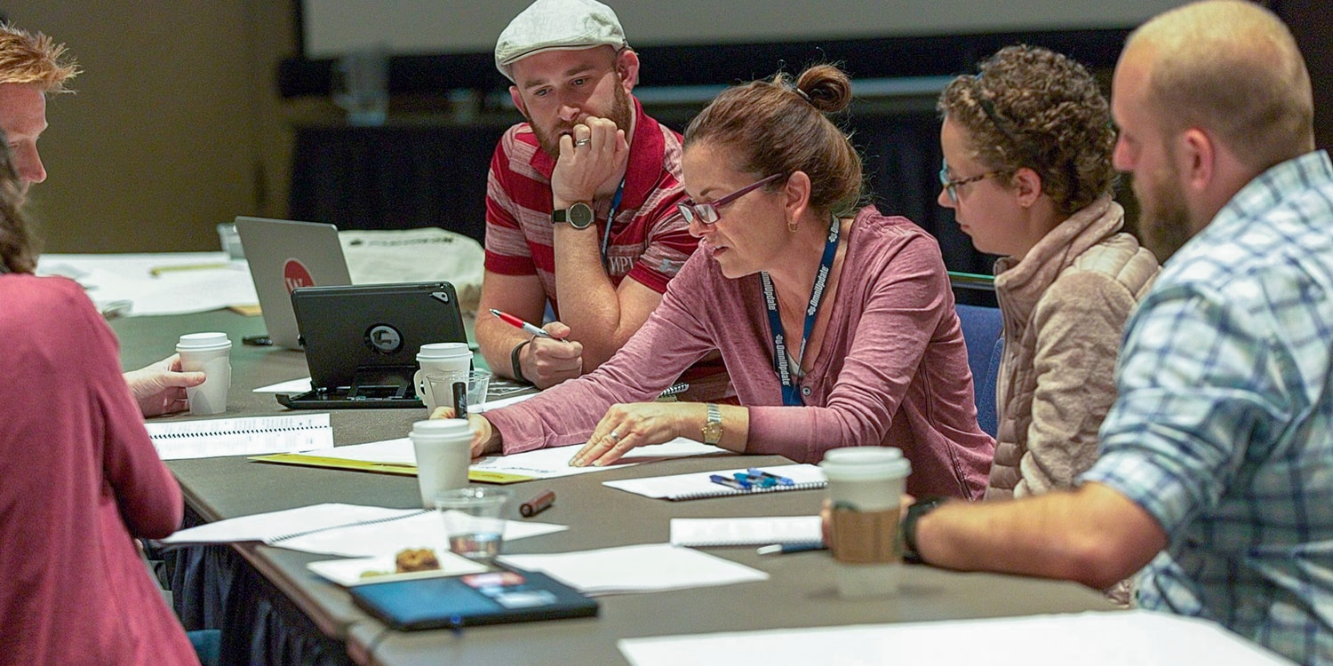 HighEdWeb attendees write down ideas on a large notepad, they are fueled by coffee